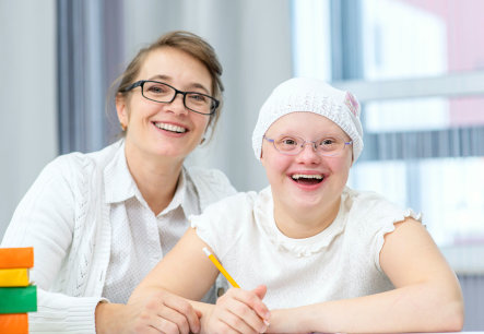 two adult woman wearing eyeglasses smiling