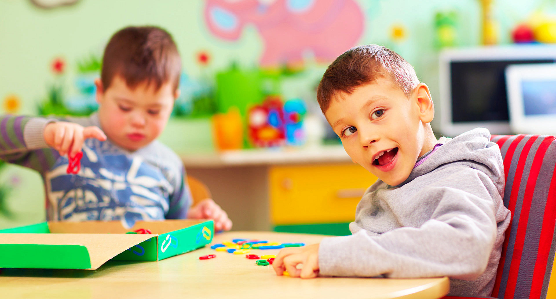 cute kids with special needs playing with developing toys while sitting at the desk
