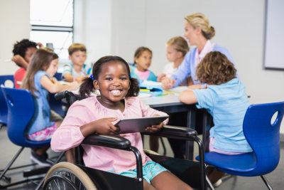 young girl in a wheelchair holding a digital tablet and children at the back doing activities