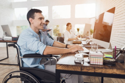 adult man in the wheelchair works in the office at the computer