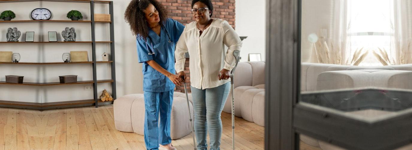 female nurse assisting senior adult woman walking