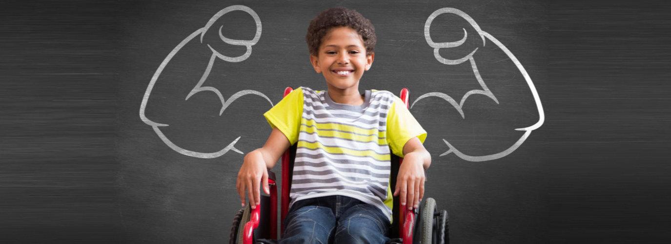 little boy sitting in wheelchair smiling